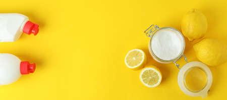 Jar of acid powder, lemons and detergents on yellow background