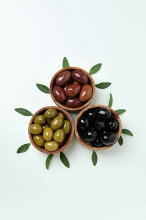 Wooden bowls of olives and leaves on white background