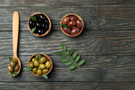 Bowls of different olives and spoon with olives on wooden background 스톡 콘텐츠