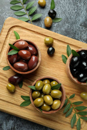 Board with olives and leaves on black smokey background 스톡 콘텐츠