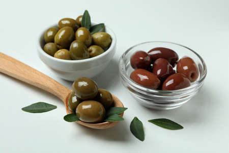 Bowls and spoon of olives, and leaves on white background