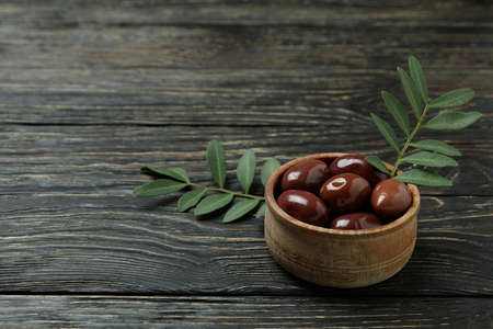 Bowl of red olives, and twigs on wooden background