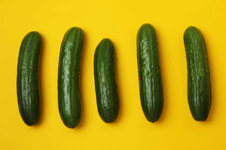 Group of fresh ripe cucumbers on yellow background 스톡 콘텐츠