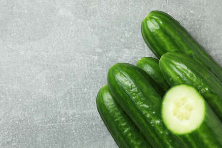 Ripe cucumbers on gray background, space for text
