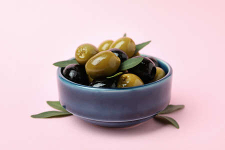 Bowl of olives and leaves on pink background 스톡 콘텐츠