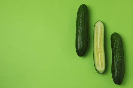 Three fresh ripe cucumbers on green background