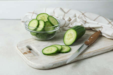 Concept of ripe vegetable with cucumbers on white textured table