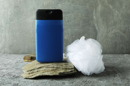 Bottle of shower gel and washcloth on gray textured table