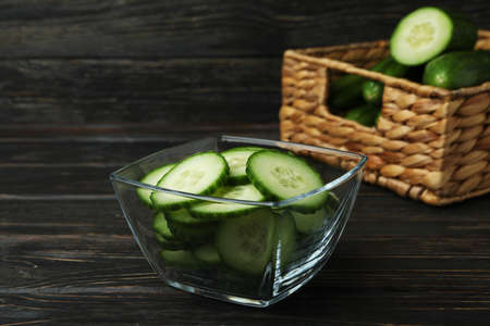 Bowl and basket with ripe cucumbers on wooden background 스톡 콘텐츠