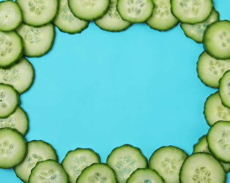 Fresh ripe cucumber slices on blue background, space for text