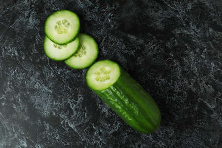 Ripe cucumber and slices on black smoky background