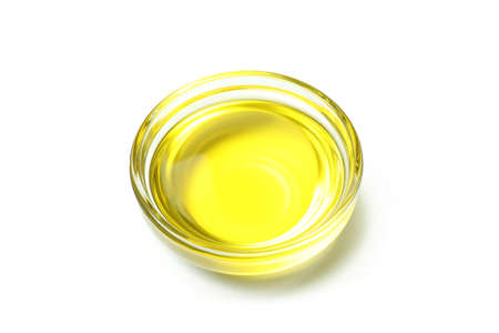 Glass bowl of olive oil isolated on white background