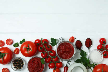 Bowl and jar with tomato paste on white wooden background with ingredients