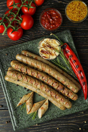 Concept of tasty food with grilled sausage on wooden table
