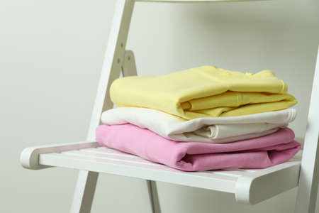 Wooden chair with yellow, pink and white sweatshirts