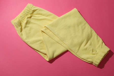 Folded yellow sweatpants on pink background, top view