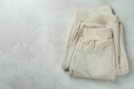 Folded sweatpants on white textured background, space for text