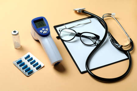 Medical tools and thermometer gun on beige background