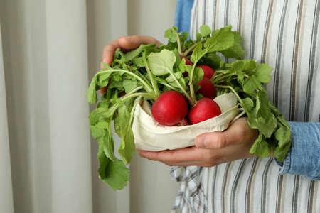 Woman hold bag with fresh radish, close up