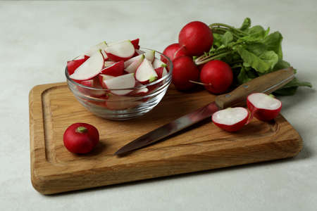 Cutting board with radish on white textured background, close up