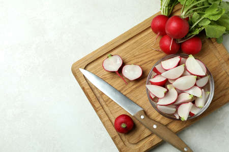 Cutting board with radish on white textured background, space for text