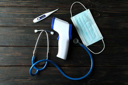 Medical concept with thermometer gun on wooden background