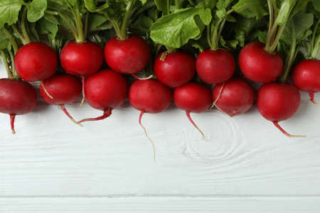 Fresh radish on white wooden background, space for text