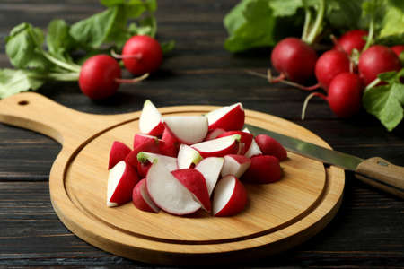 Cutting board with chopped radish on wooden background Banque d'images