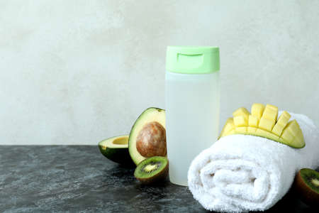 Natural shower gel, towel and ingredients on black smokey table