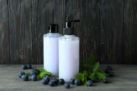 Shower gels and blueberry against wooden background
