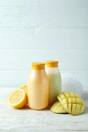 Shower gels, mango and lemon on white wooden background