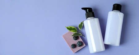 Shower gels, soap and blueberry on violet background
