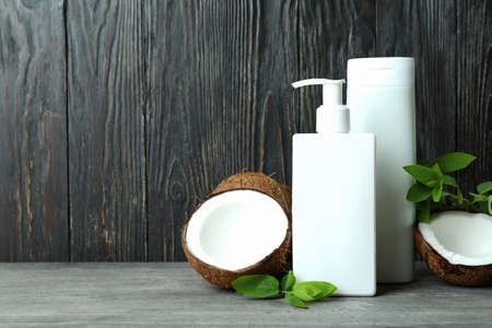 Shower gels and coconut against wooden background