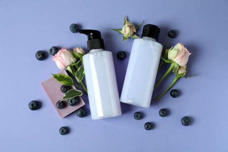 Natural shower gel and ingredients on violet background