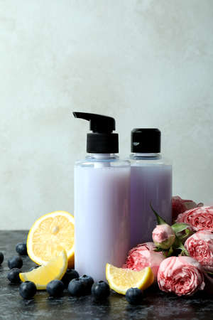 Natural shower gels and ingredients against white textured background