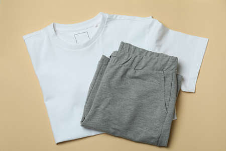 T-shirt and sweatpants on beige background, top view Banque d'images