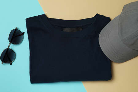 T-shirt, cap and sunglasses on two tone background