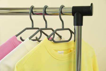 Wardrobe rack with sweatshirts against beige background
