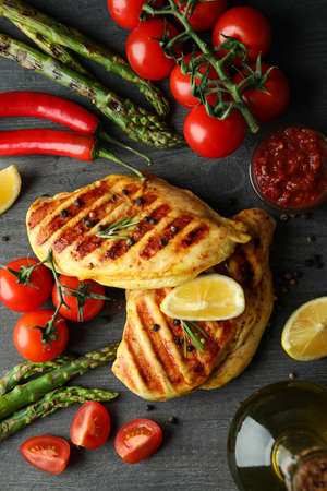Concept of delicious food with grilled chicken meat on dark wooden background
