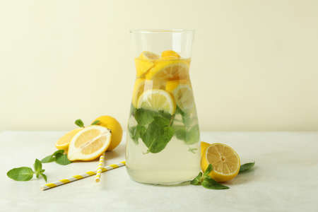 Jug of lemonade, lemons and straws on white textured table Banque d'images