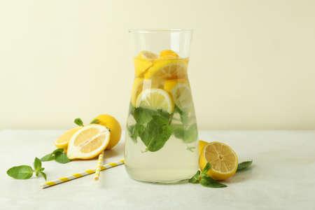 Jug of lemonade, lemons and straws on white textured table Imagens