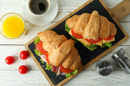 Concept of tasty eating with croissant sandwich, top view