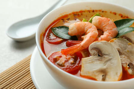 Plate of tasty Tom yum soup, close up Stock Photo