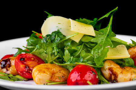Salad with shrimp and cheese on black background