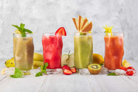 smoothies with fruit on a white wooden backdrop