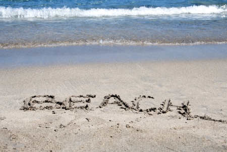 The word beach written in the sand on a beach photo