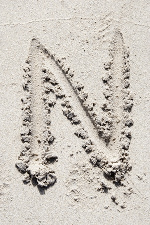 sand writing: The letter N of the alphabet writing on the sand beach
