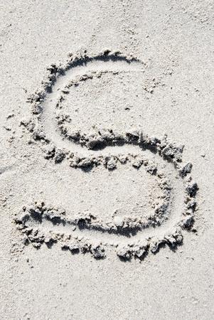s alphabet: The letter S of the alphabet writing on the sand beach