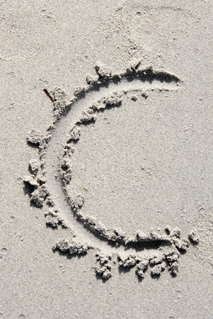 The letter C of the alphabet writing on the sand beach photo