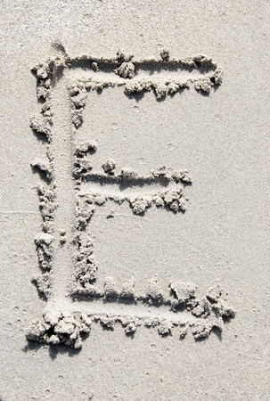 letter e: The letter E of the alphabet writing on the sand beach